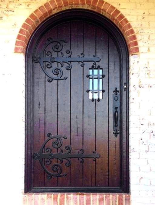 Rustic Front Door featuring a Dark Single Rounded Composite Iron Wood Door with No Glass Emtek Locksets Gothic Veritcal Planks