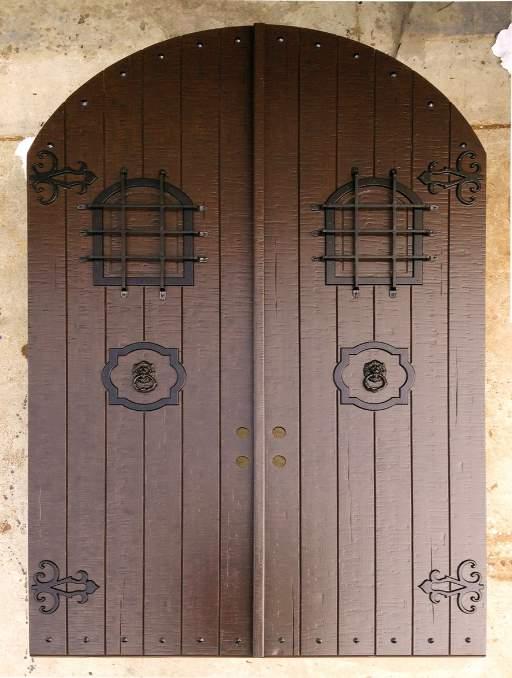 Rustic Front Door featuring a Dark Double Arched Composite Iron Wood Door with No Glass Emtek Locksets Vertical Planks