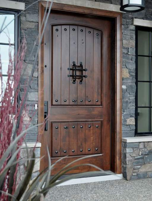 Rustic Door featuring a Dark Single Rectangular Composite Iron Wood Door with No Glass Emtek Locksets